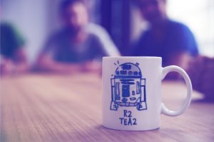 A photography of a mug with R2D2 printed on it